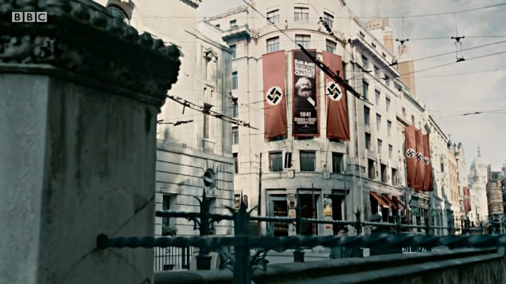 A still from the first episode of SS-GB shows a banner bearing Karl Marx's image alongside Nazi banners superimposed with a hammer and sickle.
